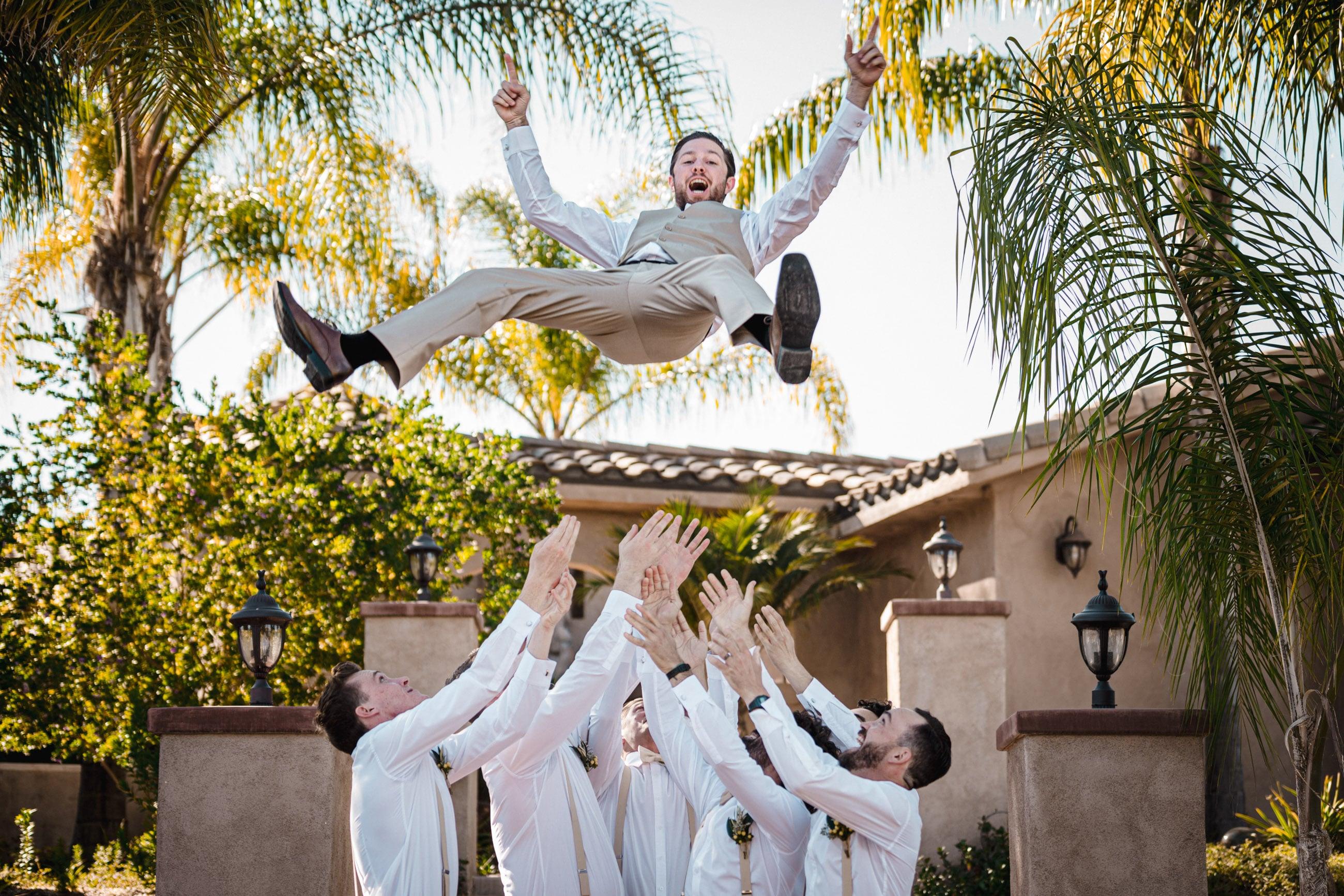 groom thrown in the air by groomsmen fun